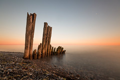 calm and cloudless (Marc McDermott) Tags: longexposure evening summer water neutraldensity pilings lakeontario sunset moon crescent canada ontario beach rocks stones sand calm cloudless smooth tranquil sky beautiful horizon