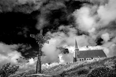 "fine art black & white of a cross-roads cross and uphill, Chapelle Notre dame de la Garde, Étretat, Seine-Maritime, Haute-Normandie, Normandy, France (grumpybaldprof) Tags: clouds blacksky mood moody atmosphere cross crossroads étretat seinemaritime hautenormandie normandy france arches ""portedaval"" ""portedamont"" ""portedemanneporte"" laiguille ""theneedle"" ""eugèneboudin"" ""gustavecourbet"" ""claudemonet"" ""paysdecaux"" ""alabastercoast"" ""chapellenotredamedelagarde"" ""thewhitebird"" ""loiseaublanc"" ""lachapellenotredamedelagarde"" ""falaised'amont"" ""thegardensofetretat"" ""lesjardinsd'etretat"" alabaster white cliffs needles bw blackwhite ""blackwhite"" ""blackandwhite"" noireetblanc monochrome ""fineart"" ethereal striking artistic interpretation impressionist stylistic style contrast shadow bright dark black illuminated ""wideangle"" ultrawide canon 70d ""canon70d"" tamron 16300 16300mm ""tamron16300mmf3563diiivcpzdb016"""