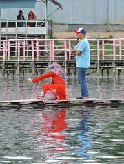 A couple of couples (A. Yousuf Kurniawan) Tags: couple red woman hijan lake water reflection streetphotography colourstreetphotography banjarbaru borneo kalimantan jetty