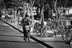 Lonely Cyclist (petemenzies.com) Tags: blackandwhite streetphotography people hoian vietnam travel asia lonely cyclist bicycle monochrome bikes streetportrait candid d700 70300mm