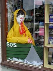 Marske scarecrows 2018 SOS (Nekoglyph) Tags: marskebythesea cleveland scarecrow festival 2018 village seaside maritime nautical hardware shop window yellow boat shark fin sos green raincoat net