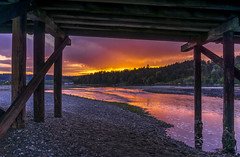 Fire in the Sky (Paul Rioux) Tags: outdoors sunset evening orange fire clouds esquimalt lagoon bridge water waterfront river flow pilings trees prioux