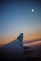 troposphere (Lithium Pears) Tags: 35mm film analogue analog canoneos300v canonef50mm primelens filmphotography analoguephotography filmneverdies airplane wing moon dawn sunrise troposphere sky airplanewindow airplanewing lomographycn100 lomofilm