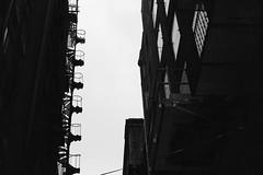 escape in style (KevinIrvineChi) Tags: fire escape building pittsburgh pa en pennsylvania sony dscrx100 alley stairs spiral staircase windows brick monochrome monochromemonday blacka blackwhite blackandwhite noiretblanc sky urban pgh negativespace light cloudy overcast dark bnw bw