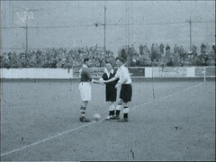 Coin Toss at a Football Match in Halifax, West Yorkshire (HalifaxArchvie) Tags: football match coin referee players game sport halifax stands crowd footballers 1950s fifties stadium old 50s bw pitch