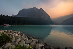 Hazy Lake Louise Sunset (NickSouvall) Tags: lake louise banff national park canadian rockies orange yellow gold hazy smokey sunset glowing light calm turqoise water soft color blue rocky coast cloudy mountains landscape nature