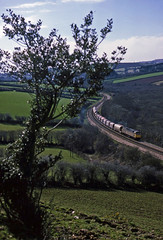 47292 hauls  the St.Blazey-Severn Tunnel Junction ABS past Tywardraeth, Par, on 3April1986. The wagon behind the loco contains seaweed. (mikul44171) Tags: tywardraeth par abs 47292 stblazey seaweed holly