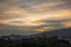 Ghostly Flames (Matt Molloy) Tags: mattmolloy timelapse photography timestack photostack movement motion sunset colourful sky clouds trails lines orange yellow thin ghostly glow light mountains silhouette apartments buildings city trees chiangmai thailand landscape lovelife