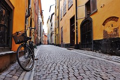 Gamla Stan (Douguerreotype) Tags: sverige door bicycle orange cobblestones sweden buildings stockholm street yellow architecture city urban wall historic bike