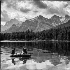 Interlopers (greenschist) Tags: banffnationalpark people alberta herbertlake forest water mountain blackwhite canada lake trees boat glaciers