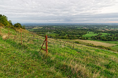 Village Below (Geoff Henson) Tags: view vista panorama village houses hill slope fence wire posts grass sky cloud tree horizon distance