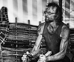 Wicker and Woodwork (Neil. Moralee) Tags: middevonshow2018neilmoralee neilmoralee man craft craftsman wicker wood shave spoke beard glasses hair vest tattoo sweat sweaty work working mid devon show neil moralee nikon bandw blackandwhite candid face photography contrast monochrome monotone mono bw urban black white life portrait people gritty street faces strangers d7200 tough muscles tendons sinew fence tools