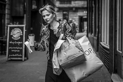 The Shopping Expedition (Leanne Boulton) Tags: monochrome portrait urban street candid portraiture streetphotography candidstreetphotography candidportrait streetportrait streetlife woman female lady shopping bags coffee hands tone texture detail depthoffield bokeh naturallight outdoor light shade city scene human life living humanity society culture people lifestyle alley alleyway canon canon5dmkiii 70mm ef2470mmf28liiusm black white blackwhite bw mono blackandwhite glasgow scotland uk