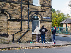 Saltaire 003 (Peter.Bartlett) Tags: window unitedkingdom people facade olympuspenf westyorkshire wall urbanarte hat man urban streetphotography candid uk m43 can lunaphoto standing microfourthirds sign peterbartlett corner men shipley england gb