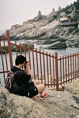 Double take. (romy_clair) Tags: camera rocks ocean sea coloir portrait colour color man tourist busan south korea asia travel analogue amateur film 35mm