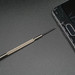 Small screwdriver and broken smartphone on dark background