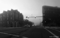 Pipestone and Wall Streets, Benton Harbor (mswan777) Tags: mobile iphone iphoneography michigan bentonharbor apple outdoor white black monochrome car cityscape urban line architecture building light street intersection mist morning fog city