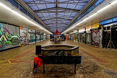 Umbrella..ella..ella (Geoff Henson) Tags: umbrella brolly precinct mall shop derelict graffiti bench planter notice lights roof paving walkway pedestrian person man pigeon bird