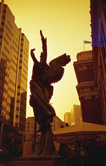 The Ascent (Yutaka Seki) Tags: angel soldier statue heaven sky buildings pentaxmesuper smcpentaxa35mmf20 fujicolorsuperiaxtra800 homedeveloped unicolorpresskit redscale film analogue vancouverbc waterfront