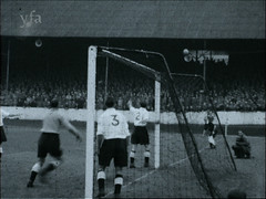 Football Match in Halifax, West Yorkshire (HalifaxArchvie) Tags: football match crowd footballers defenders halifax 1950s fifties goal goalpost net stadium sport game players old bw pitch