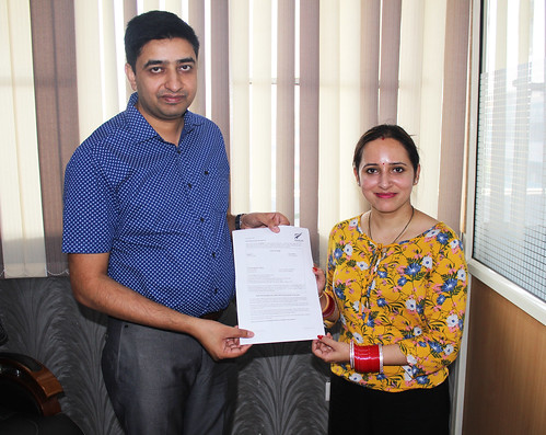 Mr. Gurvinder Kang (Director of West Highlander) handing over New Zealand Dependent Visitor Visa to Pushpa Joshi