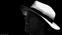 Black and white and bright light (Neil. Moralee) Tags: italyneilmoralee neilmoralee dark light bright woman face portrait profile classic mature hat smile teeth bw blackandwhite bandw mono monochrome lady close trilby sunshine blackbackground shade shadow italy people neil moralee olympus omd em5 contrast