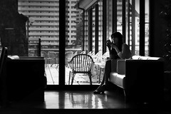 Where are you now? (明遊快) Tags: window seat room chair lobby bench waiting monochrome contrast woman light shadows reflections blur japan japanese lines candid