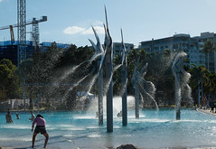 Poolside @ Cairns (Marian Pollock) Tags: queensland australia water cairs shoreline pool waterfeature spray sculpture people highlights buildings crane
