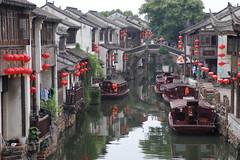 七里山塘街 (沐均青) Tags: chinese travel summer china historical cultural lotus green water lake reflections rock buildings white arch bridge lantern red boat yellow people