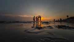 Friends at the sea-side (Marta Panzeri) Tags: tramonto sunset mare sea spiaggia seaside sand sabbia reflection riflesso cielo sky people persone friends contrast contrasto amici sunbeam water acqua holiday vacanza wideangle grandangolo