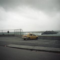 taxi stand (Tom Kondrat) Tags: taiwan analogue film mamiya6 mediumformat 120 6x6 kodakportra160 before typhoon typhoonblues tomkondrat calmbeforethestorm taxi ocean parking yellow maria