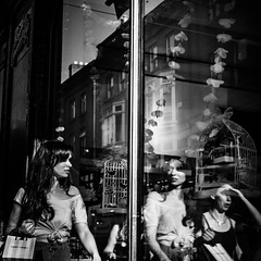 Looking glass (Kieron Ellis) Tags: woman women window glass reflection bag cage necklace contrast bright shadow candid street blackandwhite blackwhite monochrome
