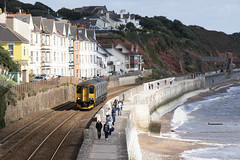 Along the sea wall: Dawlish, Devon (Dai Lygad) Tags: trains railways railroads class150 dieselmultipleunits dmu 150248 gwr greatwesternrailway green seaside seawall dawlish cardiffcentraltopenzance england uk unitedkingdom september 2018 beach walkers people flickr stock photos photographs images pictures jeremysegrott cliffs geotagged forwebsite forwebpage forblog forpowerpoint forpresentation