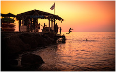 Children Jumping off a Pier at Sunset (Heathcliffe2) Tags: children kids people divers jumping leaping playing pier beach sunset sunrise sea greece crete agia marina fun play silhouette sun colour nightfall twilight childhood flag