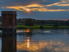As Summer Ends (Ian M Bentley) Tags: sywellcountrypark sywellreservoir lake pond northampton wellingborough england uk eveningsun olympus omd em1ii tamron140150mm megazoom wideangle zoom dam 1920s watertower valvetower northamptonshirecountycouncil reflections water orange goldenhour goldensun golden yellow amber sunset rays beams stillwaters outdoor sky clouds serene solice september 2018 autumn dusk landscape waterscape trees silhouette