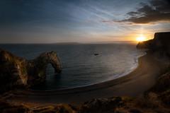 A Ray of Sunshine (janinelee66) Tags: dorset durdledoor sunset light sunlight sun rays beach rocks sea water person bay