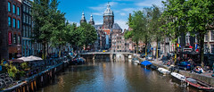 2018 - Amsterdam - St. Nicolaaskerk (Ted's photos - Returns Late November) Tags: 2018 amsterdam cropped nikon nikond750 nikonfx tedmcgrath tedsphotos vignetting stnicholasbasilica stnicholasbasilicaamsterdam sintnicolaaskerk sintnicolaaskerkamsterdam umbrellas bikes bicycle bridge church churchdome churchspires boats canal
