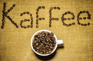 Filled Coffee Cup with Kaffee sign in the Background