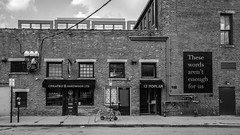 Poplar St. (tim.perdue) Tags: poplar st short north arts district columbus ohio downtown urban city street storefront door window brick wall building mural public art these words arent enough for us created hardwood ltd sidewalk curbbicycle scooter awning parking meter sign black white bw monochrome panasonic gx7 lumix 1232mm