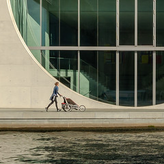 Arc with mother (Adaptabilly) Tags: berlin shadow woman travel sidewalk window river walking water germany architecture stroller column europe sky circle lumixgx7