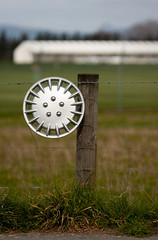 20180906_0164_40D-200 Lost and Found (249/365) (johnstewartnz) Tags: christchurchinternationalairport christchurch chc wheelcap hubcap post fence canon canonapsc apsc eos 40d canon40d canoneos40d 70200mm 70200 70200f28 onephotoaday oneaday onephotoaday2018 365project project365 249365 day249