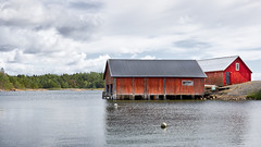 Boatsheds (Jaanus Remm) Tags: midday noon åland finland summer sea seascape sky clouds forest water coast norrgård västrasimskäla red