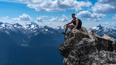 Resting Hiker (Sworldguy) Tags: whistlermountain hiking cliff rocky rugged clouds mountains tourism view alpine summit sonya73 summer sitting edge britishcolumbia canada whistler seatosky