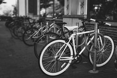 White Bike (Bicycle Series No. 16) (briburt) Tags: rad fahrrad briburt fuji fujifilm xt2 xf35mm 35mm blackandwhite acros bw monochrome filmsimulation bike bokeh bikes skyline cambridgesidegalleria bicycle white wheels bright cycling cycle contrast playful massachusetts boston cambridge recreation sport whitebike movement energy blur architecture urban city bigcity summer