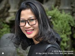 2018-03b Vietnam's Beauty (52) (Matt Hahnewald) Tags: matthahnewaldphotography facingtheworld people character head face eyes eyeglasses mouth teeth lips lipstick expression lookingcamera smile longhair hairstyle consent emotion living lifestyle beauty style hanoi vietnam asia asian vietnamese southeastasian individual female adult young woman photo nikond3100 primelens nikkorafs50mmf18g 50mm horizontal street portrait closeup headshot threequarterview sidewaysglance black outdoor color vignette postprocessing editing posing posingcamera awesome smiling beautiful attractive elegant stunning captivating charming classy fabulous soulful curlsattheend curledends clarity sunlight blownouthighlights