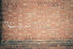 smiles on the wall (johnnytakespictures) Tags: disposable disposablecamera singleuse smile pocketsocket 35mm film analogue leamingtonspa leamington warwickshire street smiling smiles graffiti art paint wall brick bricks