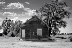 Timken, Kansas (unknown quantity) Tags: clouds sky trees monochrome barewood abandonedhouse corrugated grass shadows railroadtracks horizon fadedpaint peelingpaint blackandwhite weathered cloudsstormssunsetssunrises