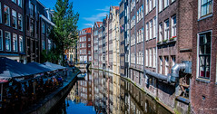 2018 - Amsterdam - Canal Side Cafe (Ted's photos - For Me & You) Tags: 2018 amsterdam cropped nikon nikond750 nikonfx tedmcgrath tedsphotos vignetting canal canalscene bridge umbrellas reflection waterreflection buildings