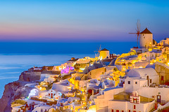Traveling and New Destinations Concepts. Romantic Sunset at Santorini Island in Greece. Image Taken in Oia Village At Dusk. Amazing Sunset with White Houses and Windmills in Frame. (DmitryMorgan) Tags: landscape aegean architecture aurora bluehour building caldera church cityscape destination dusk europe european famous greece greek hellenic historic holiday island iya landmark mediterranean mountain oia oya panoramic picturesque resort rock romantic santorini scenery sky slope summer summit sunlight sunny thera tourism town traditional traveling twilight view village volcano windmill