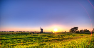 The Sun looking at a beautiful old Dutch mill.